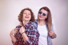 Zwei schöne Freundinnen, die glücklich lachen und ein fil aufpassen Stockbilder