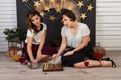 Zwei schöne Freundinnen durch den Kamin lizenzfreies stockbild