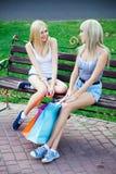 Zwei schöne Freundinnen mit Einkaufenbeuteln stockbilder