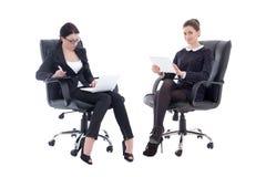 Zwei schöne Geschäftsfrauen, die auf Bürostühlen mit Tabelle sitzen Stockfotos