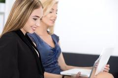 Zwei schöne Geschäftsfrauen, die auf Seminar sitzen und einiges schreiben Stockfoto