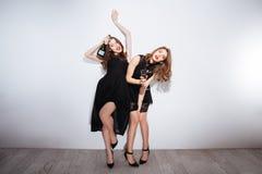 Zwei schöne getrunkene Frauen, die Champagner über weißem Hintergrund trinken Stockfotografie