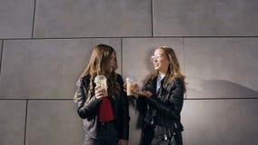 Zwei schöne glückliche Mädchen, die Cocktails bei der Stellung nahe grauer Wand neben modernem Gebäude sprechen und trinken drau? stock video footage