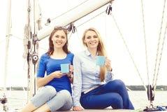 Zwei schöne, glückliche und junge Mädchen, die einen guten Sommertag auf einer Yacht genießen und einen Tee trinken Lizenzfreie Stockbilder