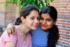 Zwei schöne indische Mädchen, die und zusammen lächeln die Kamera betrachten sitzen lizenzfreie stockfotografie