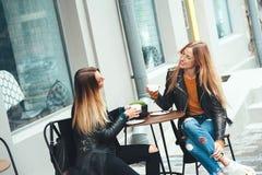 Zwei schöne junge Blondine, die Kaffee trinken und im netten Restaurant im Freien klatschen Lizenzfreie Stockfotos