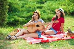 Zwei schöne junge Frauen in den Hüten auf einem Picknick, das eine Gitarre spielt und Spaß hat lizenzfreies stockbild