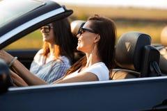 Zwei schöne junge Frauen in der Sonnenbrille sitzen in einem schwarzen Cabriolet und lächeln an einem sonnigen Tag lizenzfreie stockfotos