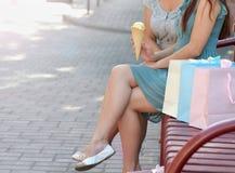 Zwei schöne junge Frauen, die auf Bank nachdem dem Einkauf und dem Essen der Eiscreme sitzen Lizenzfreie Stockfotos