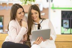 Zwei schöne junge Frauen, die auf einer Bank sitzen und betrachten Stockfotografie