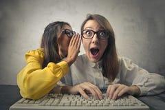 Zwei schöne junge Frauen, die bei der Stellung lokalisiert auf Weiß klatschen lizenzfreie stockbilder