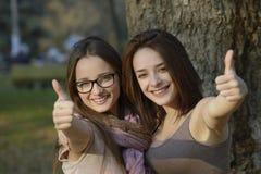 Zwei schöne junge Frauen, die Daumen geben, up Zeichen Stockfoto