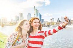 Zwei schöne junge Frauen, die ein selfie auf Frankfurt nehmen stockbild