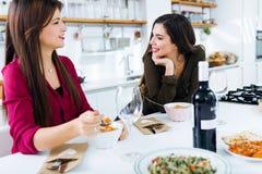 Zwei schöne junge Frauen, die Gemüsesuppe in der Küche essen Lizenzfreie Stockbilder