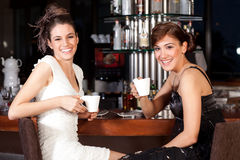 Zwei schöne junge Frauen, die Kaffee am Stab trinken stockbilder