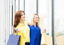 Zwei schöne junge Frauen mit Einkaufenbeuteln Lizenzfreie Stockfotos