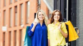 Zwei schöne junge Frauen mit Einkaufenbeuteln Stockfotos