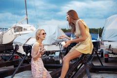 Zwei schöne junge Frauen sprechen auf Pier Stockfoto