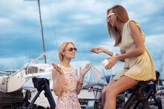 Zwei schöne junge Frauen sprechen auf Pier Lizenzfreies Stockfoto