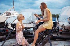 Zwei schöne junge Frauen sprechen auf Pier Stockbild