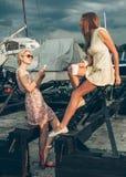 Zwei schöne junge Frauen sprechen auf Pier Stockfotos