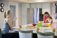 Zwei schöne junge Frauen und kleines Baby in der Küche Stockbild