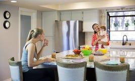 Zwei schöne junge Frauen und kleines Baby in der Küche Stockfoto
