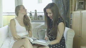 Zwei schöne junge Freundinnen, die Modezeitschrift aufpassen stock video