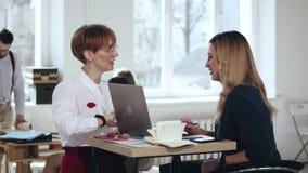 Zwei schöne junge kaukasische Managerfrauen, die Stellung am modernen modischen Bürotisch sprechen Gesunder Arbeitsplatz stock video footage