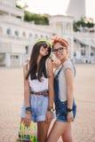 Zwei schöne junge Mädchen auf einem Skateboard in der Stadt lizenzfreie stockbilder