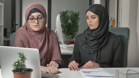 Zwei schöne junge Mädchen in den hijabs sitzen im Büro und besprechen Zeitpläne, Geschäft, Dialog, Gespräch 60 fps stock video footage