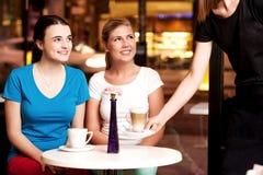 Zwei schöne junge Mädchen an der Kaffeestube Stockfotografie