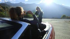 Zwei schöne junge stilvolle Mädchen machen Fotos auf einem Smartphone innerhalb eines roten Kabrioletts Lustige Fotoaufnahme im U stock video
