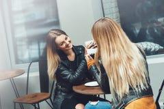 Zwei schöne Kleidung der jungen Frauen in Mode, die Unterhaltungsund trinkenden Kaffee des Restes im Restaurant im Freien trinkt lizenzfreie stockfotos