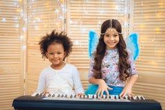 Zwei schöne kleine Mädchen in der festlichen Kleidung spielen Klavier auf Urlaubsparty lizenzfreie stockfotografie