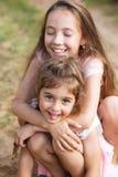 Zwei schöne kleine Mädchen, die über die Küste umfassen und lachen lizenzfreies stockbild