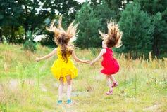 Zwei schöne kleine Mädchen, die an sonnigem Sommer d springen und tanzen Lizenzfreie Stockfotografie