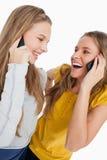Zwei schöne Kursteilnehmer, die am Telefon lachen Lizenzfreie Stockbilder
