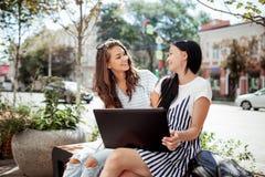 Zwei schöne lächelnde dunkelhaarige dünne Mädchen, tragende zufällige Ausstattung, sitzen an der Bank und am reizenden Blick an e lizenzfreie stockfotos