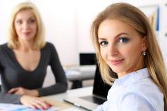 Zwei schöne lächelnde Geschäftsfrauen am Arbeitsplatz im Büro lizenzfreie stockfotos