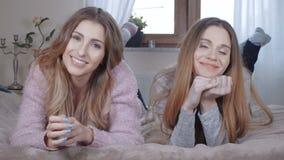 Zwei schöne lächelnde Mädchen beim Lügen auf Bett stock footage
