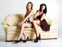 Zwei schöne luxuriöse Frauen, die auf einer Couch sitzen Stockfoto