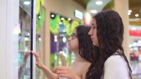 Zwei schöne Mädchen benutzen die wechselwirkende Platte, um einen Kauf im Einkaufszentrum abzuschließen stock video