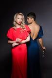 Zwei schöne Mädchen in den Abendkleidern Aufstellung, Ebene Glas halten Lizenzfreie Stockfotos
