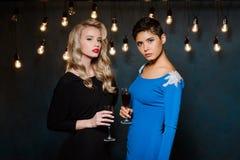 Zwei schöne Mädchen in den Abendkleidern Aufstellung, Weingläser halten Stockfotos