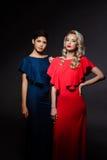 Zwei schöne Mädchen in den Abendkleidern, die über grauem Hintergrund aufwerfen Lizenzfreies Stockfoto