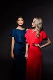 Zwei schöne Mädchen in den Abendkleidern, die über grauem Hintergrund aufwerfen Stockfotos