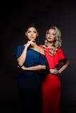 Zwei schöne Mädchen in den Abendkleidern, die über grauem Hintergrund aufwerfen Stockfoto