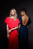 Zwei schöne Mädchen in den Abendkleidern, die über grauem Hintergrund aufwerfen Lizenzfreie Stockbilder