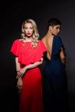 Zwei schöne Mädchen in den Abendkleidern, die über grauem Hintergrund aufwerfen Lizenzfreies Stockbild